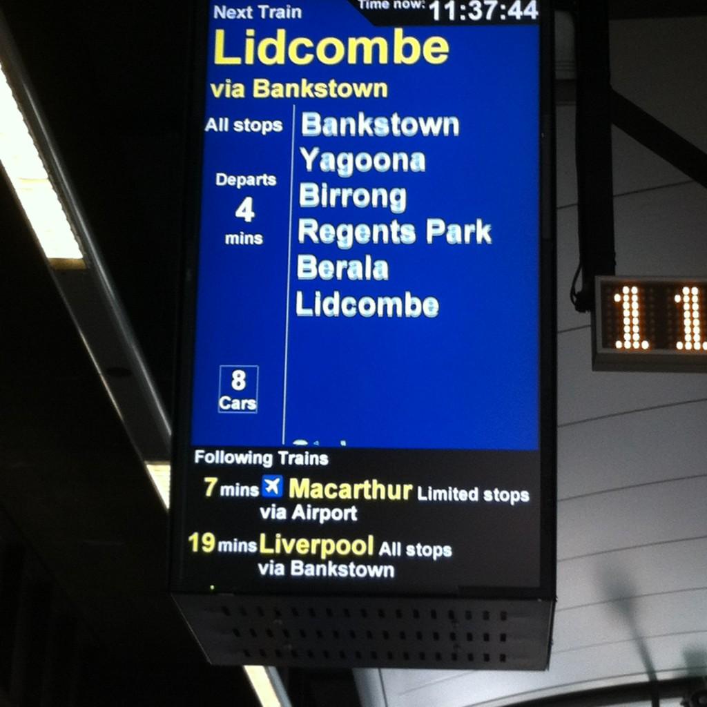 Painel na estação de Circular Quay mostrando que o próximo trem naquela plataforma passará pelo aeroporto.