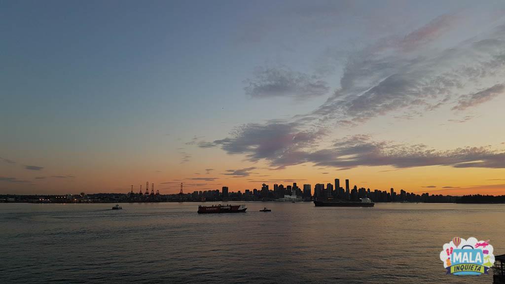 Sol se pondo atrás do centro de Vancouver, visto do Lonsdale Quay.